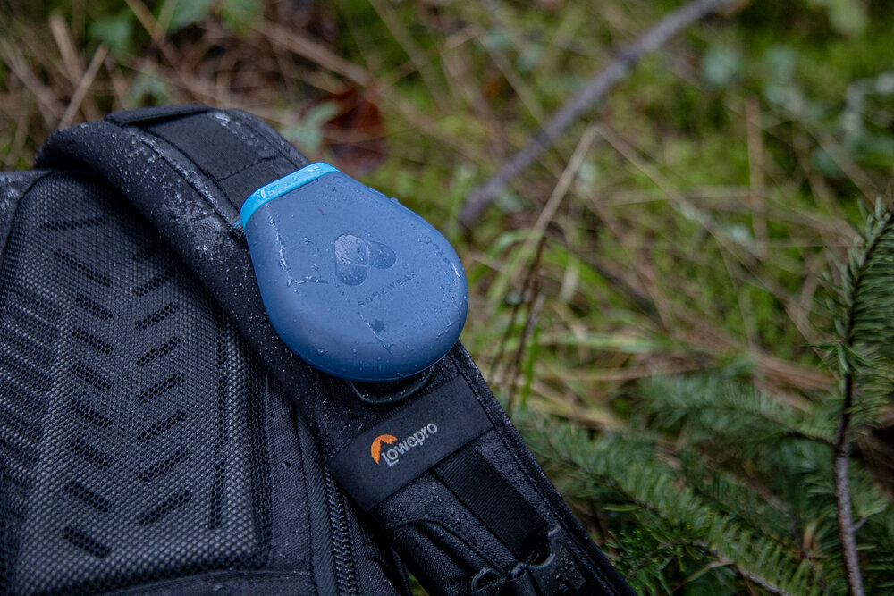 The Global Hotspot clipped to a backpack strap.